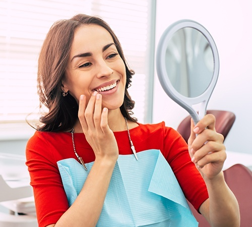 Woman in dental chair looking at smile