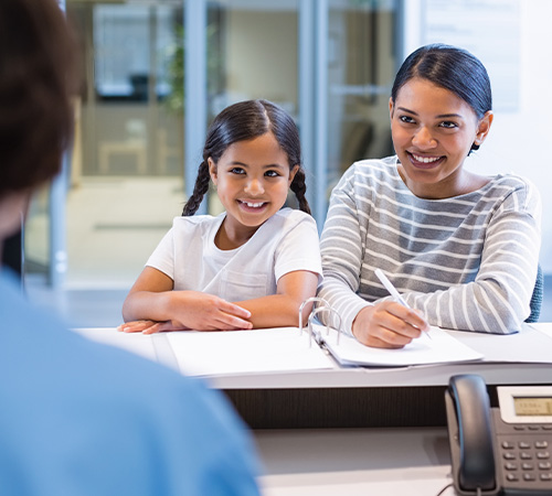 Mother and daughter checking in at dental office reception desk